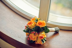 Orange bridal bouquet on a window sill Royalty Free Stock Photo