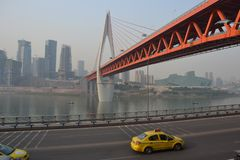 Orange Bridge in Chongquin, China w/ Taxis. Two yellow taxis pass underneath a modern orange bridge in Chongquin, China with buildings in the background Royalty Free Stock Photography