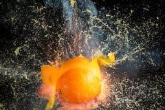 Orange bristning in i stycken på svart bakgrund fotografering för bildbyråer