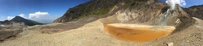 The orange brown color of the Crater during dry season at Mount Papandayan, Indonesia in panoramic view stock photography
