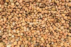 Orange brown rock pebbles background. Texture Stock Image