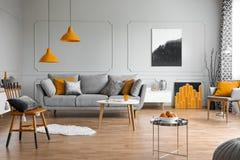 Orange brytningar i en gr? vardagsruminre royaltyfri foto