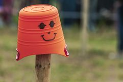A orange bucket with a drawn face royalty free stock images