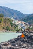 Orange Buddhist monk sitting on riverbank at Rishikesh, holy town and travel destination in India, famous for yoga classes. Clear Stock Images