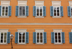 Orange building with blue opened windows Royalty Free Stock Photos