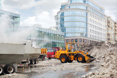 Orange bulldozer loads wet snow to trucks for snow melting. On street in city at cloudy day Stock Photo