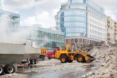 Orange bulldozer loads wet snow to trucks for snow melting Stock Photo