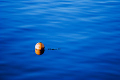 Orange buoy on blue sea water Stock Photos