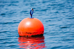 Orange buoy. Floating in blue water stock image
