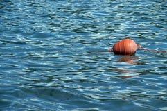 Orange buoy floating on sea. Orange marker buoy floating on blue sea or lake stock photography