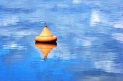Orange buoy floating on water Stock Image