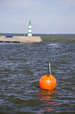 Orange buoy and lighthouse in sea dock Royalty Free Stock Photos
