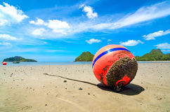 Orange buoy in the sand Royalty Free Stock Photos