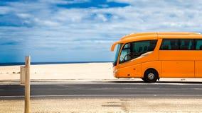 Orange bus on a road. Orange bus parked on a coastal road near the sea Stock Image