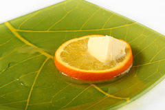 Orange and butter. The cube of a butter kindled on a hot orange stock photography