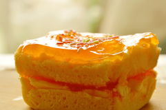 Orange butter cake topping colorful candy on chop block Stock Photography