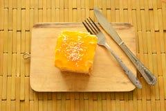 Orange Butterkuchen, der bunte Süßigkeit mit Gabel ein Messer auf hölzernem Hiebblock übersteigt Stockfotos