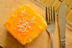 Orange Butterkuchen, der bunte Süßigkeit mit Gabel und Messer auf hölzerner Hiebplatte übersteigt Stockfoto