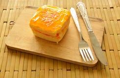 Orange Butterkuchen, der bunte Süßigkeit mit Gabel und Messer auf Hiebplatte übersteigt Lizenzfreie Stockfotos