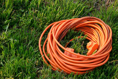 Orange cable in the grass. Orange electric cable put in green grass Royalty Free Stock Photos