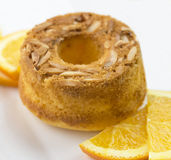 Orange Cake with Almond slithers. A round orange cake decorated with almond slithers and sliced oranges in front and behind it Royalty Free Stock Image