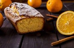 Orange cake on the corn flour with orange liqueur. Orange cake on the corn flour with the orange liqueur on the dark wooden background with oranges and cinnamon Stock Images