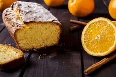 Orange cake on the corn flour with orange liqueur. Orange cake on the corn flour with the orange liqueur on the dark wooden background with oranges and cinnamon Stock Photography
