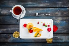 Orange cake with a cup of tea fresh raspberries on a white plate with rose petals. Top view. Beautiful wooden background. Orange cake with a cup of tea fresh Royalty Free Stock Photography