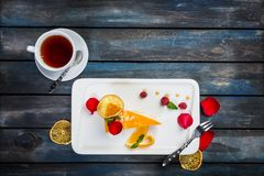 Orange cake with a cup of tea fresh raspberries on a white plate with rose petals. Top view. Beautiful wooden background. Orange cake with a cup of tea fresh Royalty Free Stock Photos