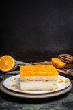 Orange cake with fruit icing over dark rustic background, side view Royalty Free Stock Photography