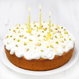 Orange cake with Greek yogurt, honey and pistachios with candles Stock Image