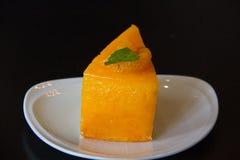 Orange cake with orange topping. In wooden dish Stock Image