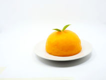 Orange cake. Is placed on a white plate. And adorned with green leaves Royalty Free Stock Photos