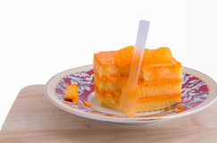 Orange cake in plate on background Royalty Free Stock Photography