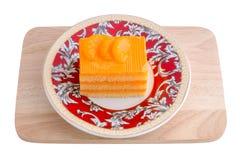 Orange cake in plate on white background Stock Photos