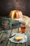 Orange cake with retro mood on an old bag. Retro mood photo for an orange cake on an old green bag laying on the wooden table nest of a glass cup of tea and cake Stock Images