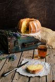 Orange cake with retro mood on an old bag. Retro mood photo for an orange cake on an old green bag laying on the wooden table nest of a glass cup of tea and cake Stock Image