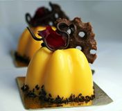 Orange cake with rose petal and chocolate decor and black sesame stock images