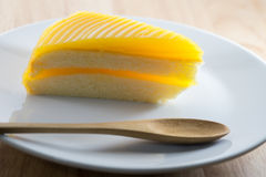 Orange cake. On the white plate with wooden spoon Royalty Free Stock Images