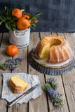 Orange cake on wooden background. And cup full of Oranges, and slice of the orange cake on a piece of Arabic newspaper Royalty Free Stock Photo