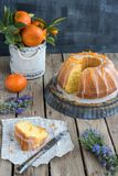 Orange cake on wooden background. And cup full of Oranges, and slice of the orange cake on a piece of Arabic newspaper Royalty Free Stock Image
