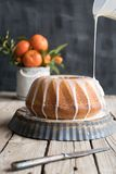 Orange cake on wooden table and dark background. With doping white icing on top of the cake Royalty Free Stock Photo
