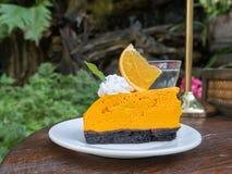Orange cake on wooden table. In garden Stock Photos