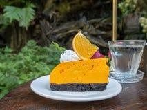 Orange cake on wooden table. In garden Royalty Free Stock Photos