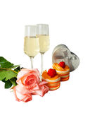 Orange cakes, glasses of champagne, pink roses  and  gift box isolated Royalty Free Stock Images