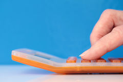 Orange Calculator with Fingers Closeup on Blue Royalty Free Stock Images