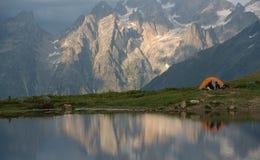 Orange camp  and tourists near mountain lake Stock Photos