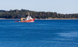 Orange Canadian Coast Guard Cutter on Blue Water. An orange Canadian coast guard boat on deep blue water near Halifax, Nova Scotia Royalty Free Stock Image