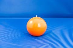 Orange candle. Beautiful orange candle on a Blue background Stock Photos