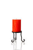 An orange candle on a black holder. Royalty Free Stock Photos